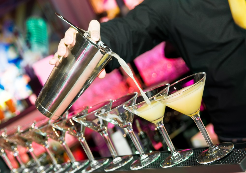 Barman hand with shake mixer pouring cocktail into glasses arranged in a line
